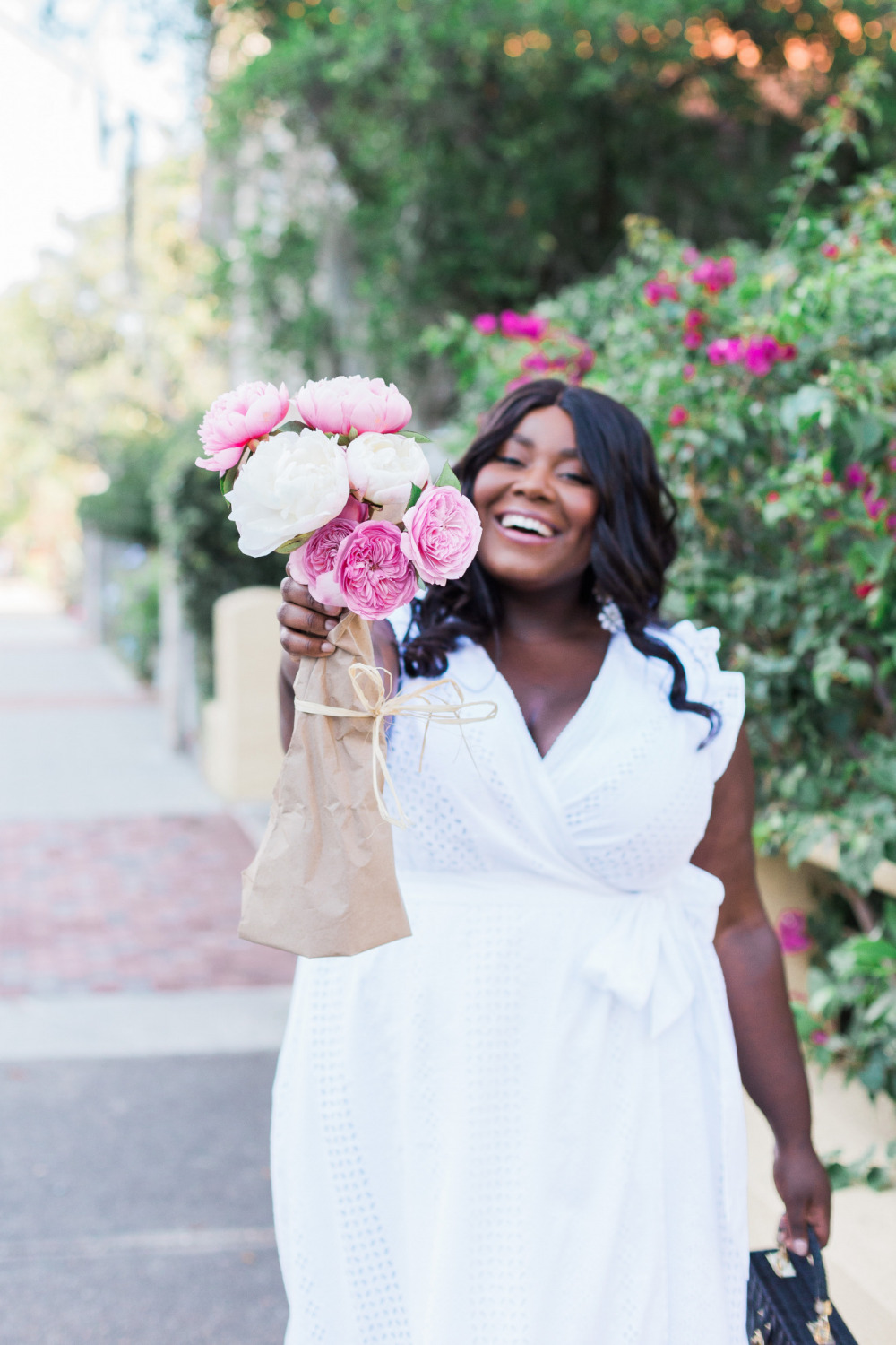 Black woman holding bouquet of pink peonies. Black woman holding bouquet