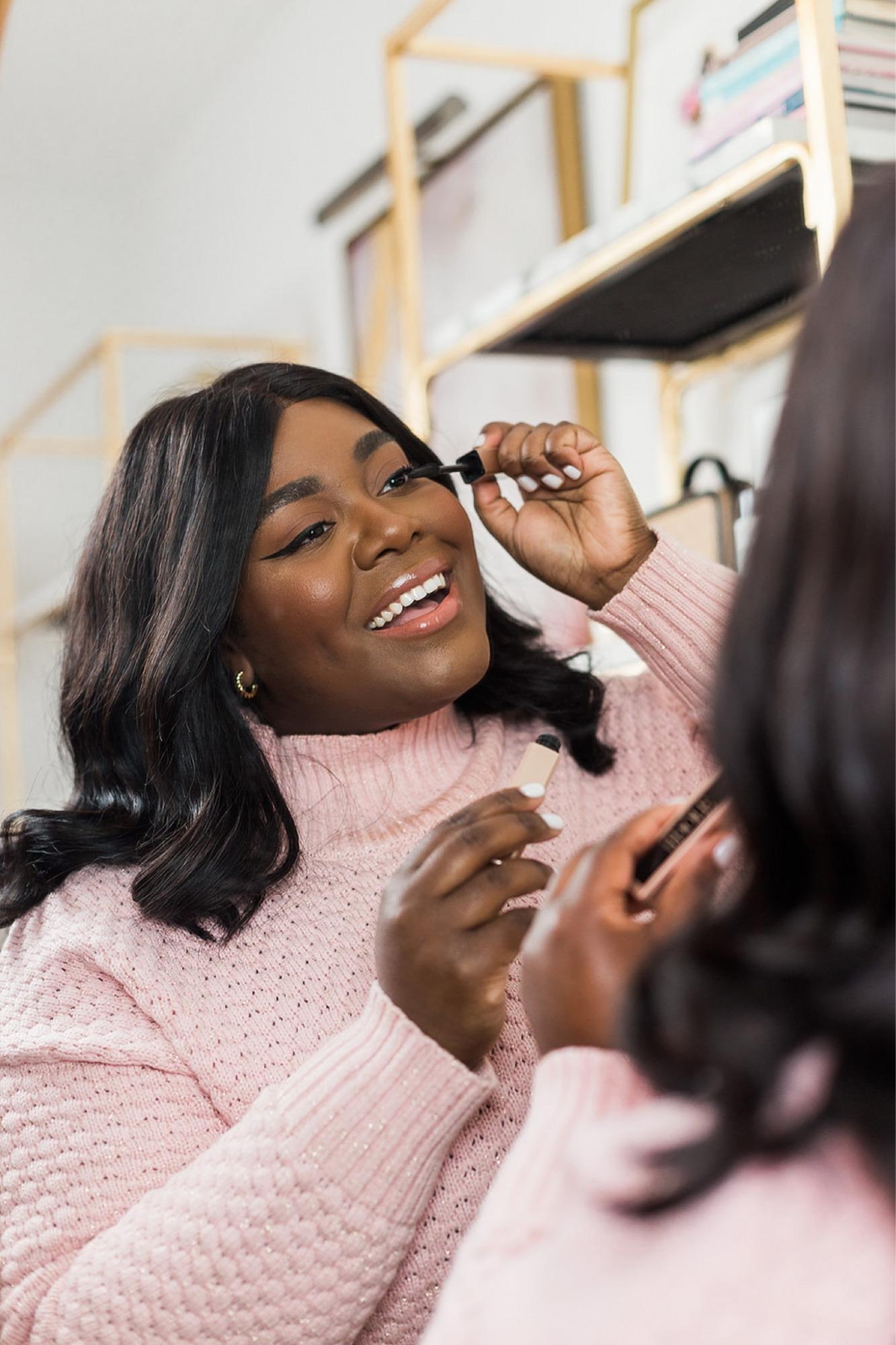 Black woman putting on makeup.  Black woman smiling putting on mascara.  Black Woman doing morning makeup routine.